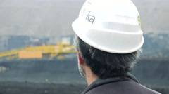 Worker looks on building site with machines - close-up worker from behind Stock Footage
