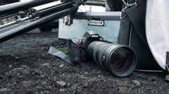 Camera lies on ground near by tripod and bag Stock Footage