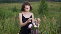 Fresh flowers in a stylish drawer. Beautiful brunette in a flowery field in the Stock Footage