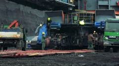 Green trucks, machines and worker work on building site Stock Footage
