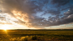 Time lapse - Clouds race towards rising sun on prairie morning Stock Footage