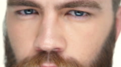 Man with red beard looks straight at camera - stock footage