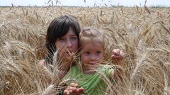 Mellow wheat harvest - cute family mother and child daughter play in a field Stock Footage