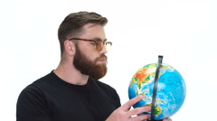 Man examines the globe in his hands Stock Footage