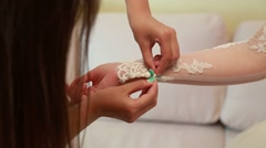Bridesmaid makes bow-knot on the back of brides wedding dress Stock Footage