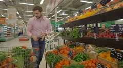Young couple doing shopping in the greengrocer, steadycam shot Stock Footage