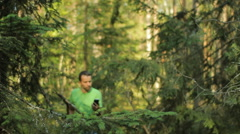 A man walks through the forest with the phone and looks at the navigation Stock Footage