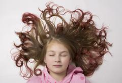 Red-haired teenager girl lying on the floor with her hair form a circle Stock Photos
