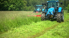 Two light blue tractors are working on the field of grass and are cutting it Stock Footage