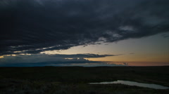 Time lapse - Clouds move towards horizon over prairie pond at sunrise Stock Footage