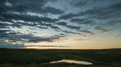 Time lapse - layers of clouds glow as sun rises over horizon to shine on pond Stock Footage
