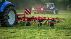 Tractor is moving grass with a mower conditioner Stock Footage