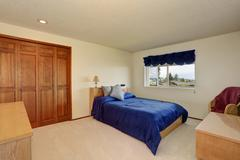 Nice bedroom in creamy tones with blue bedding, built in wardrobe and carpet  - stock photo