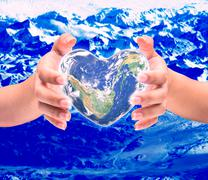 World in heart shape with over women human hands on blurred natural backgroun Stock Photos