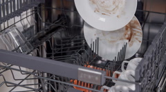 Slowly putting dirty dishes in the dishwasher Stock Footage