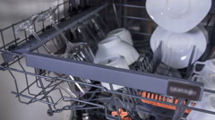 Putting saucers in the dishwasher Stock Footage