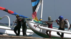 Men carrying a jukung (balinese fishing boat) at Amed beach Stock Footage