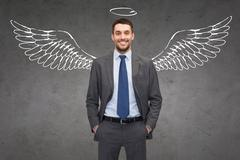 Smiling businessman with angel wings and nimbus Stock Photos