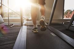 Close up of man legs walking on treadmill in gym Stock Photos