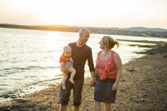 Family of three person is standing on sunset and sea backdrop Stock Photos