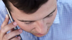 Handsome man smiling on phone call in outdoors - stock footage