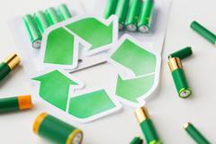 close up of batteries and green recycling symbol - stock photo
