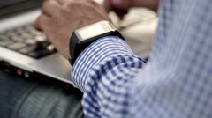 Close up of man check his smart watch with laptop - stock footage