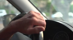 Close up of a man's hand on steering wheel - driving thru the city Stock Footage
