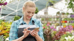 Female florist uses her smartphone at the garden centre - stock footage