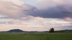 Time lapse - purple clouds flow over foothills of Montana mountains Stock Footage