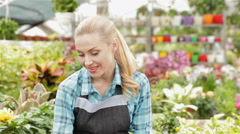 Female florist smells red and white flowers at the garden centre - stock footage