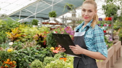 Female florist holds black tablet at the garden centre Stock Footage
