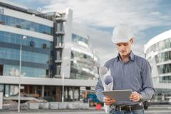 Portrait of confident young architect or chief engineer uses digital tablet at - stock photo
