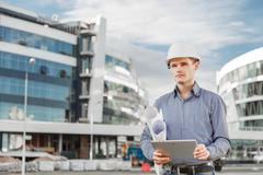 Portrait of young architect or chief engineer uses digital tablet at the - stock photo