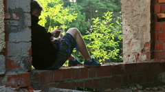 Teenager sits on the ruins of a brick old building Stock Footage