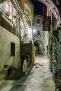 Narrow cobbled street in old town Peille at night, France. - stock photo