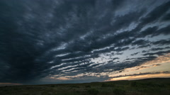 Time lapse - rows of clouds pass towards rising sun at dawn Stock Footage