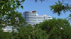 Multi-storey building in the green tree branches Stock Footage