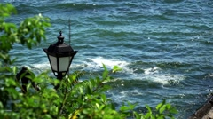 Sea shore. Sea view trees, breakwater and lamp Stock Footage