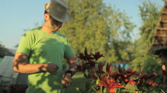 Man touching smart watches around flowerbeds flowers early in the morning Stock Footage