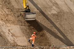 Digger works at new road construction site - stock photo