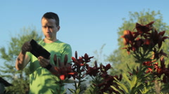 A young man is playing on a tablet near flowers early in the morning Stock Footage