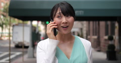 Young Asian woman in city walking street happy talking on cell phone - stock footage