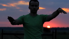 The man is dancing: does wave his arms on the background of a beautiful sunset Stock Footage