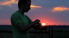 A man looks and touch smart watch at sunset. Beautiful red sky and the sun Stock Footage