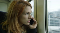 Commuter on her way to work looking out of the window and using smartphone - stock footage