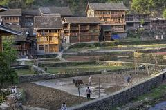 Ethnic village in China mountainous terrain, wooden houses at sunset. Kuvituskuvat