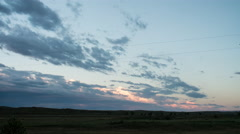 Time lapse - rose colored storm clouds at sunset over flat prairie Stock Footage