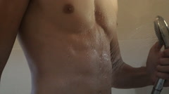 Athletic guy taking bath under shower Stock Footage