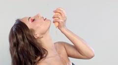 Girl squashes half grapefruit up Stock Footage